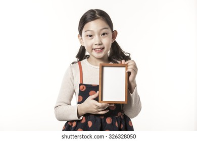 A asian(japan, chinese, korea) pretty girl hold a blink(empty) photo frame with a smile isolated white at the studio.