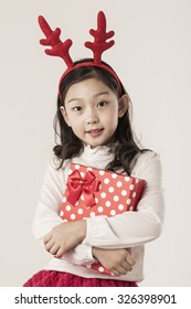 A asian(japanese, korean, chinese) girl(kid, children) hold a gift box(paper bag) for christmas(xmas) at the studio.