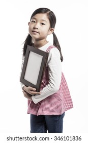 A asian(korean, japanese, chinese) girl(kid, student, child, woman, female) wearing pink skirt and denim pants stand up with a wood photo frame for friend and family isolated white.