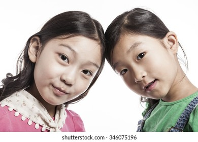 A asian(korean, japanese, chinese) girls(kid, student, child, woman, female) wearing green shirts and pink blouse make a pose together with smile isolated white.