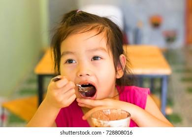 Asian,Little girl is eating ice cream.