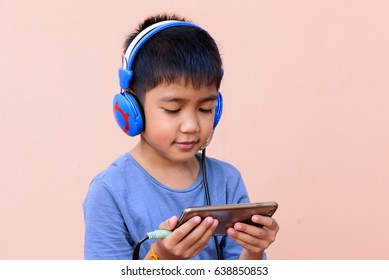 Asian's boy watching and listening to movie in mobile phone.Happy and relaxation time for a children.