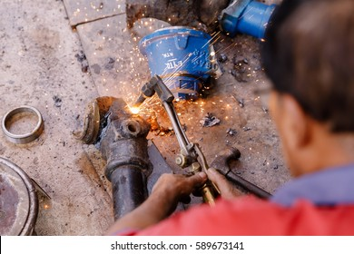 Asians Craftsman being using gas welding steel in a factory.