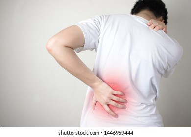 Asians with pain after lifting something heavy using both hands to catch his backIsolated on white background.