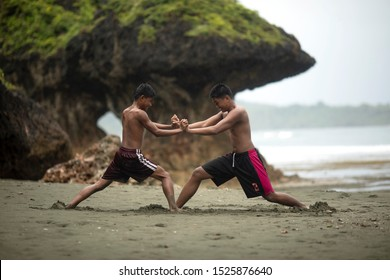Asians teens fighting on the beach. Young men wrestle. Filipino boys playing on the beach.