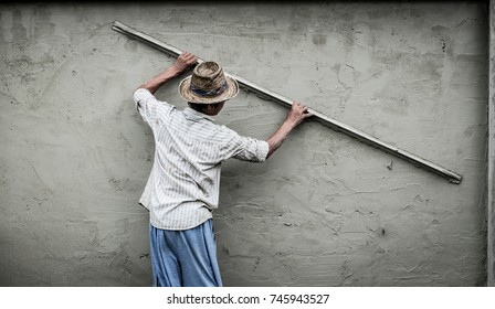 Asian/thai worker screeding cement wall with screed, aluminium cement triangle trowel, Concrete Tool Supply.