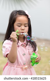 asin girl blowing bubbles