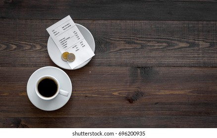 Ask for the bill at restaurant. Bill and coins near cup of coffee on wooden table top view copyspace