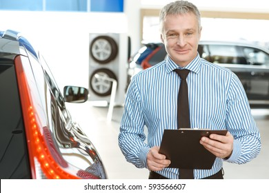 Ask me anything! Cheerful mature salesman smiling holding his clipboard standing near a new car at the car dealership salon copyspace profession professional career job occupation manager agent seller