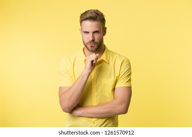 Asking himself. Handsome young man keeping hand on chin while stand yellow background. Existentialism concept. Hard question. Moral question difficulties. Listen to yourself. Question without answer.