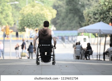 ASL affected young man on a wheel chair in the street among other people. Empty copy space for Editor's text.