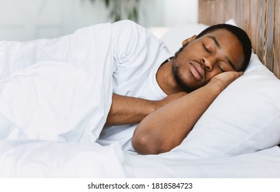 Asleep African American Guy Sleeping Resting Peacefully In His Comfortable Bed At Home, Lying With Eyes Closed. Recreation, Deep Male Sleep, Time To Rest And Nap Concept.