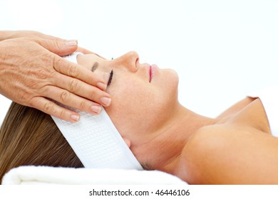 Asleep woman relaxing with a head massage in a spa center