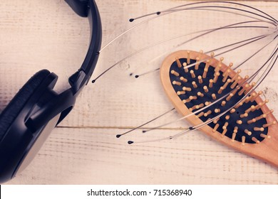 ASMR concept background. Head massage tool, Wooden Scalp and hair Massage brush and earphones. Relaxation and anti stress activities