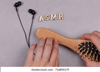 ASMR concept. Female hand holding Head massage brush and earphones. Relaxation and anti stress activities