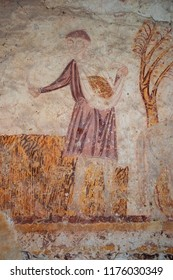 ASNIERES-SUR-VEGRE, FRANCE - AUGUST 9, 2018:  Peasant making the harvest. Fragment of rural scene (flight to Egypt theme) in Saint-Hilaire church famous for its remarkable medieval wall paintings.