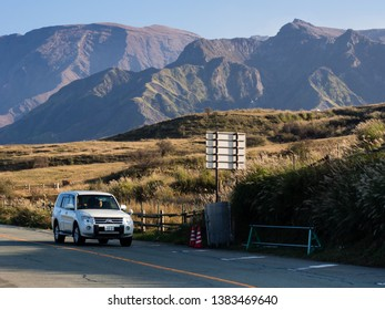 Aso, Japan - November 5, 2016: Car driving along the scenic road in Aso volcanic caldera, part of Aso-Kuju National Park