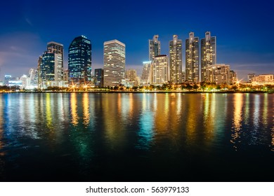 Asoke modern buildings of Bangkok night city skyline, Thailand. Cityscape photography of Benchakitti Park at dusk. Bangkok night city downtown. Modern night city skyline with lights reflection, Asia