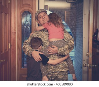 Asoldier man is coming home in the door and hugging his children for a love, family or reunited concept.