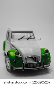 Aspang, Austria - July 3, 2018: Isolated classic white and green Citroen 2CV being lit from the top, with a plain white background.