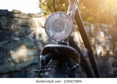 Aspang, Austria - June 25, 2018: Close up of an old city bicycle tyre with a large reflector on the mud guard, with a stone wall and trees in the background, on a beautiful sunny summer day.