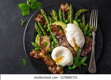 asparagus, avocado, poached egg and fried bacon  salad, top view, dark background