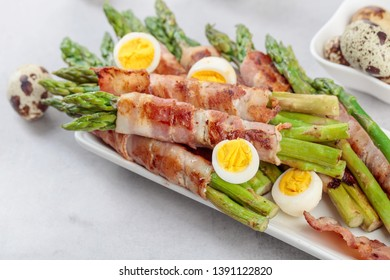 Asparagus with bacon. Green asparagus wrapped in bacon with boiled quail eggs.