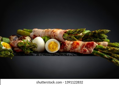 Asparagus with bacon. Green asparagus wrapped in bacon with boiled quail eggs and green onion.