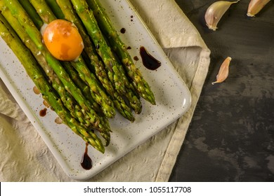 Asparagus cooked with egg served on a white ceramic tray on the table.