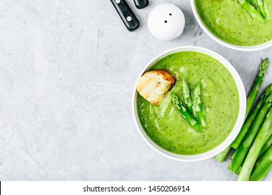 Asparagus cream soup with croutons on gray stone background, top view. Green summer vegetable soup.