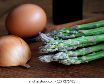 Asparagus, egg, onion on wooden background. Raw ingredients ready for cooking.