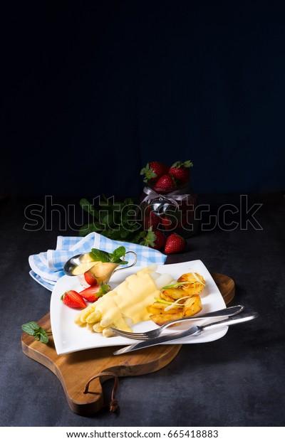 Asparagus , hollandaise sauce and baked potatoes
