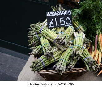 Asparagus on wooden basket for sale on food stall at fresh market with copy space