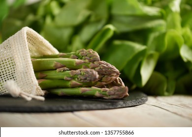 Asparagus pile out of the bag on stone plate and green salad background