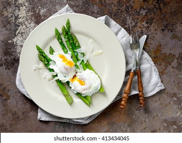 Asparagus with poached eggs seasoned with parmesan, top view