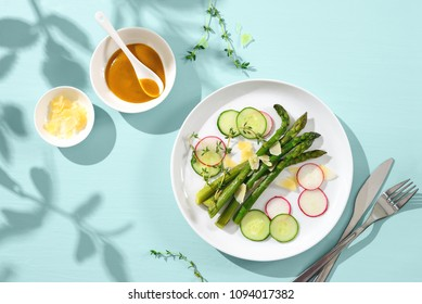 Asparagus salad served on sunny shadowed table surface, seasonal summer or spring food concept, overhead view