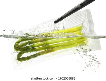 Asparagus for sous vide cooking, taking out or putting into the water; isolated on white background