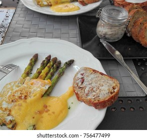 Asparagus under bechamel sauce coat with fried egg and bread with lard. Silver knife whitr plates outdoor restaurant eating hipster trendy dishes.