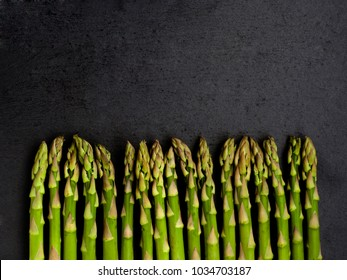 Asparagus uniformly placed vertically on natural slate surface