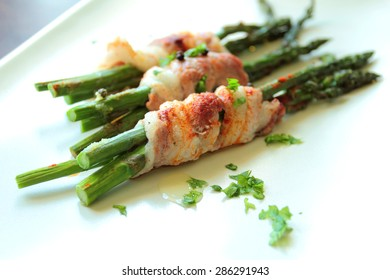 Asparagus wrapped in bacon and grilled with fresh choped parsley