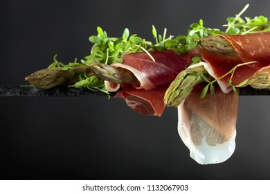 Asparagus wrapped in prosciutto with cress salad. Copy space for your text.