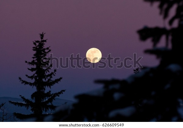 ASPEN, COLORADO - Jan. 25th, 2009 - A pristine full moon rises over the Rocky Mountains near Aspen, Colorado. Cold winter nights allow for clear skies to see the moon and stars near Aspen.