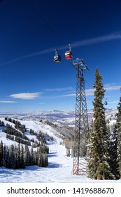 Aspen, Colorado / USA - February 24, 2019:  Aspen Mountain gondola chair lift with blue sky and winter snow on sunny day high in the Rocky Mountains