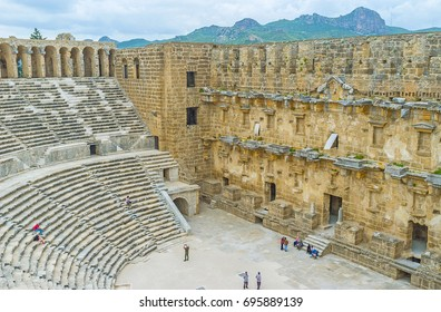 ASPENDOS, TURKEY - MAY 8, 2017: Tourists enjoy interior of ancient Aspendos amphitheater, one of the well preserved objects of Aspendos archaeological site, on May 8 in Aspendos.