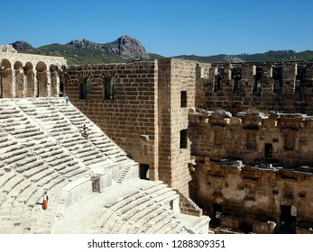 Aspendos / Turkey - October, 5th, 2017: Theater of Aspendos tribunes and front wall with some tourists. Hills in the background and the blue sky. Best preserved antique theater.