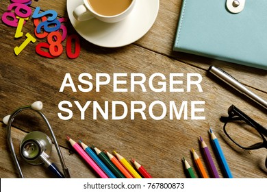 Asperger syndrome (AS) awareness concept. Top view of stethoscope,colorful pencils,coffee,notebook,pen,sunglasses,wooden numbers on wooden background written with ASPERGER SYNDROME.