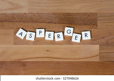 Asperger text on a wooden surface. Asperger Syndrome is a neurobiological disorder on the higher-functioning end of the autism spectrum.