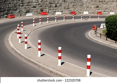 Asphalt bend and metal posts. City road.