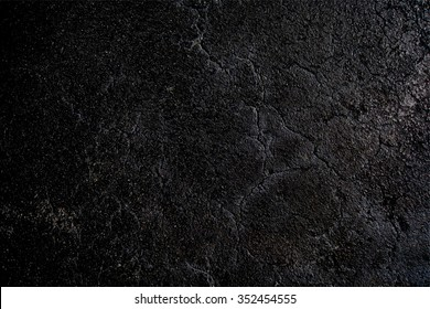 Asphalt black cracked background.  Wet old road texture. Grunge backdrop.