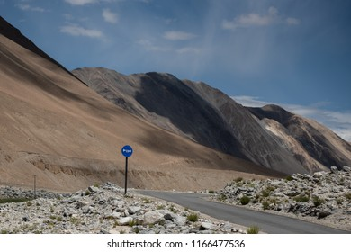 Asphalt concrete road , white rocks and horn traffic sign on the way from Leh Ladakh to Pangong lake with mountain and sky in background
